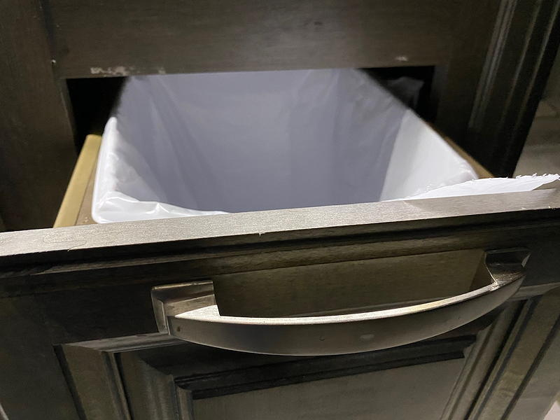 The screws holding our garbage bin's sliding rails to the surrounding cabinet had failed at the front, allowing the bin to drop.