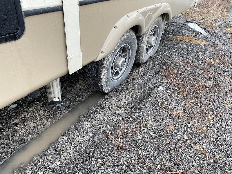 After backing our trailer into its spot at our storage yard, we discovered that the tires on one side had sunk into the gravely mud.